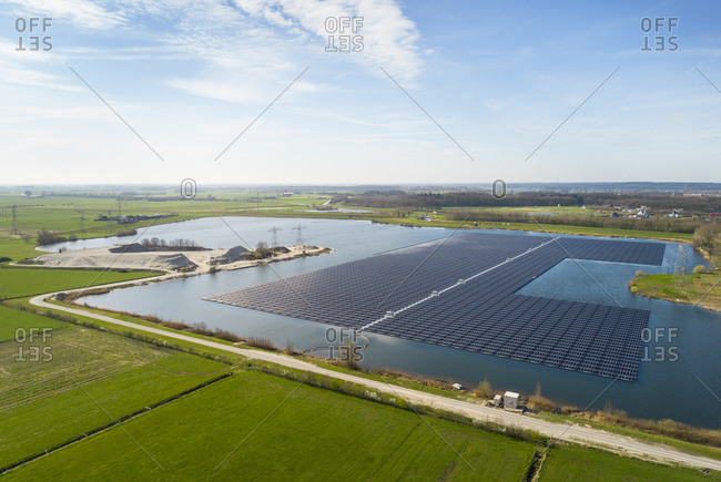 Aerial view of solar panels set on a lake in the countryside.