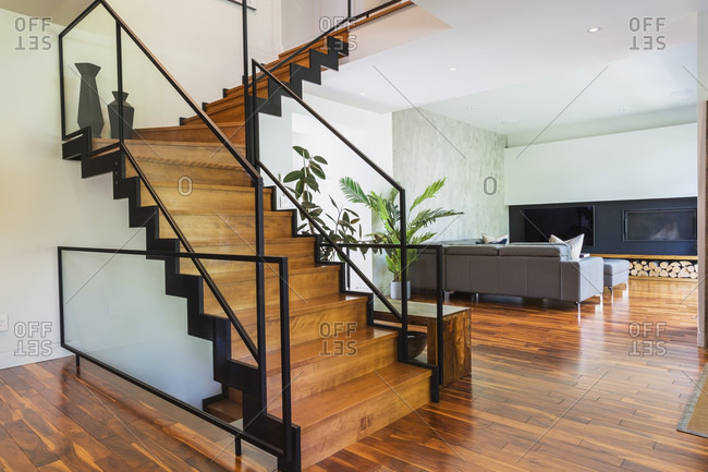 Living room with grey sofa and ottoman on a wood floor, wooden staircase with metal handrails.