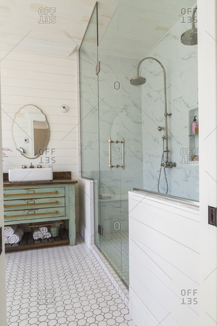 Bathroom with marbled tideland glass shower cubicle, wooden vanity unit with handbasin against cream wood paneled wall.