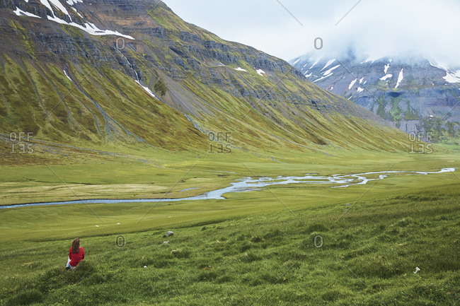 A woman sitting on a grass knoll looking down a green valley with mountains in the distance.