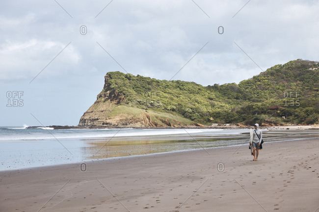 A man walking along a Nicaraguan beach with a headland in the background.