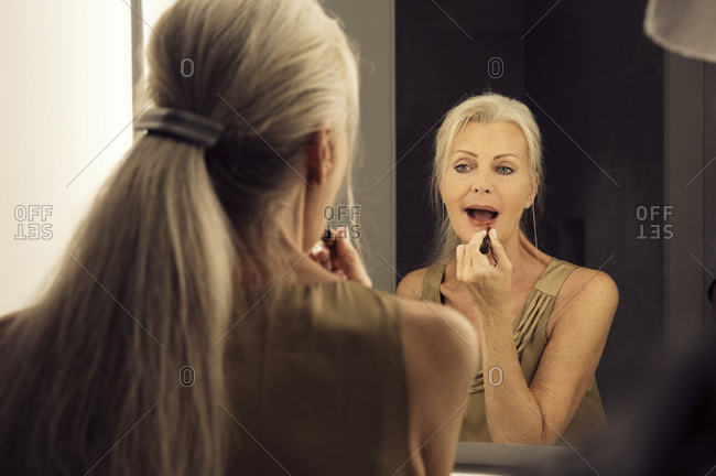 Rear view of a woman looking into a mirror and applying lipstick.