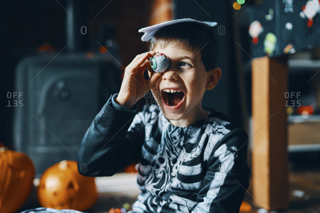 A boy dressed as a skeleton holding a chocolate wrapped as an eyeball to his eye.