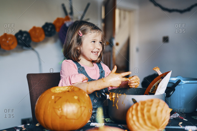 A smiling girl taking the pumpkin seeds and flesh from her fingers.