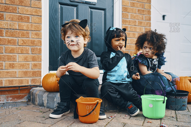 Three children dressed up for Halloween sitting on a doorstep eating sweets.