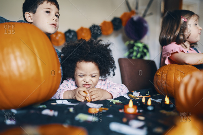 Three children at a table working on making pumpkin heads for Halloween.