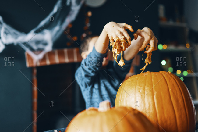 A child pulling their hands out of a pumpkin covered in seeds and pumpkin flesh.
