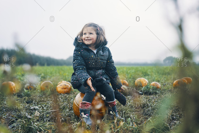 A smiling girl sitting on a pumpkin in a pumpkin field.