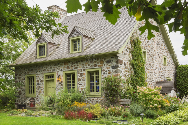 Exterior view of idyllic stone cottage with pretty garden in Canada.
