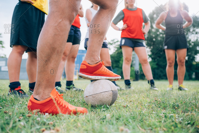 The legs and feet of a group of women standing on a training pitch one with a foot on a rugby ball.