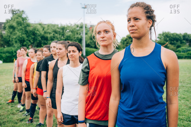 A line of women wearing sports vests in a training field during rugby training.