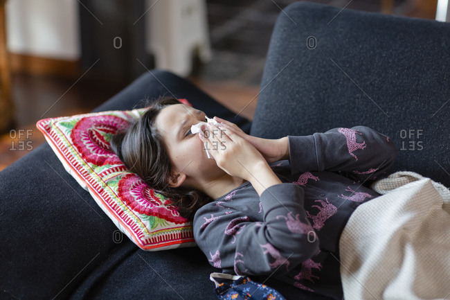 Girl lying on her back on a sofa blowing her nose.