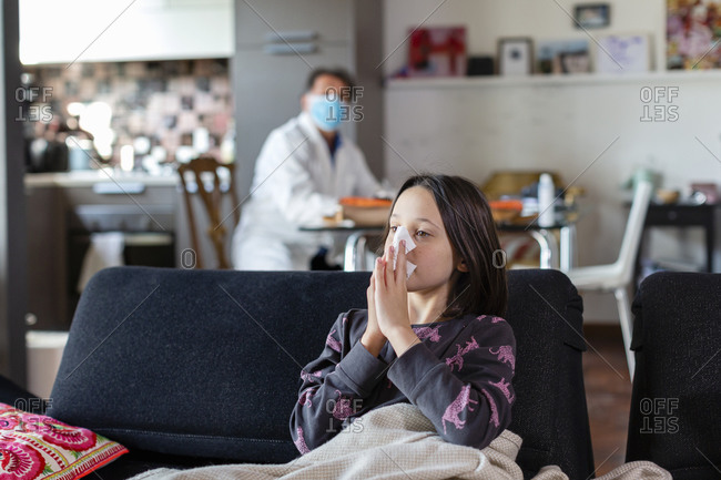 Girl sitting on a sofa blowing her nose, and a doctor seated in a face mask and white coat at a distance.