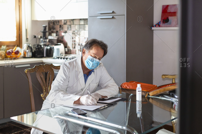 Doctor wearing a white coat, facemask and protective gloves sitting at a kitchen table writing up medical notes.