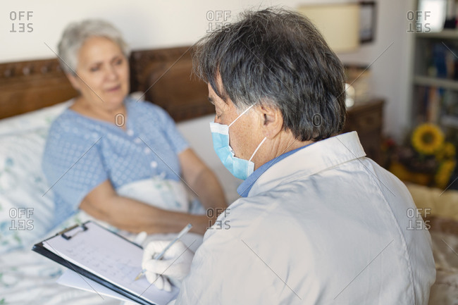 A doctor in a white coat and protective face mask making a home visit to a senior woman patient.