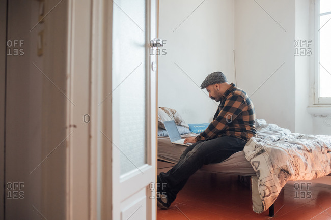 Man with big moustache wearing flat cap sitting on bed with laptop computer during Corona virus crisis.