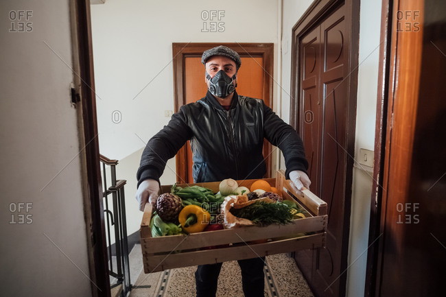 Man wearing flat cap and face mask delivering vegetable box in an apartment building during Corona virus crisis.