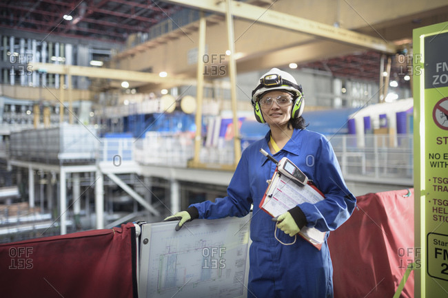 Female engineer with a clipboard and electronic monitor at work in a nuclear power station.