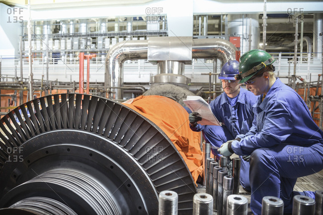 Engineer inspecting a turbine in a  nuclear power station.
