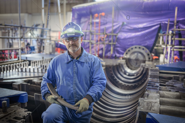 Engineer standing beside a turbine in a  nuclear power station.