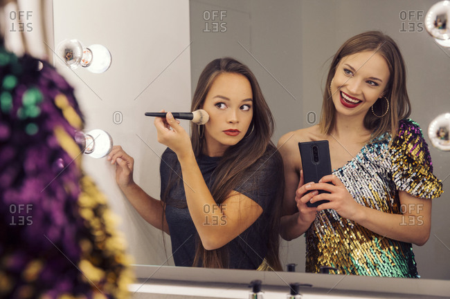 Two women putting on make up and looking in a mirror.