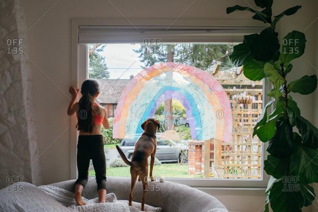 Girl draws a rainbow on the window