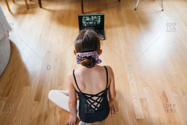 Girl watches a ballet class on her laptop