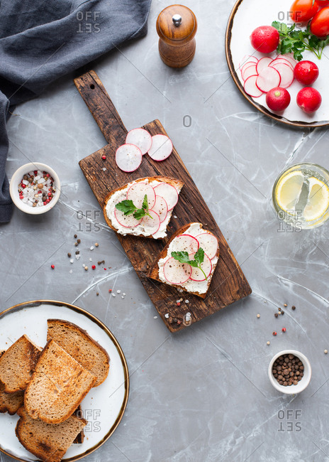 Overhead view of two open face sandwiches with fresh radish and cream cheese