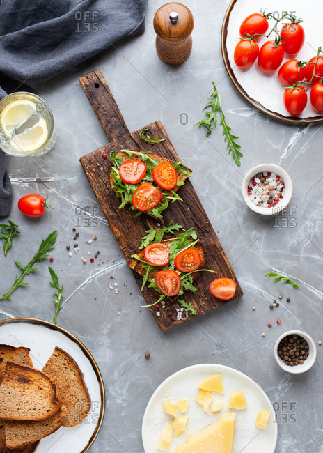 Overhead view of vegetarian open face sandwiches with fresh cherry tomatoes and arugula