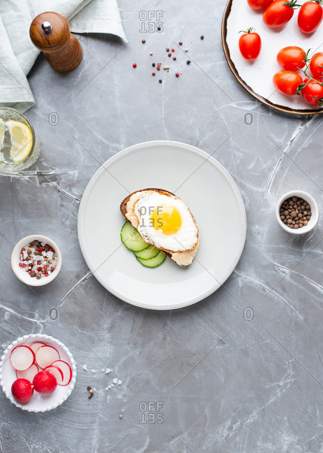 Overhead view of open face sandwich with hummus and fried egg served with fresh vegetables