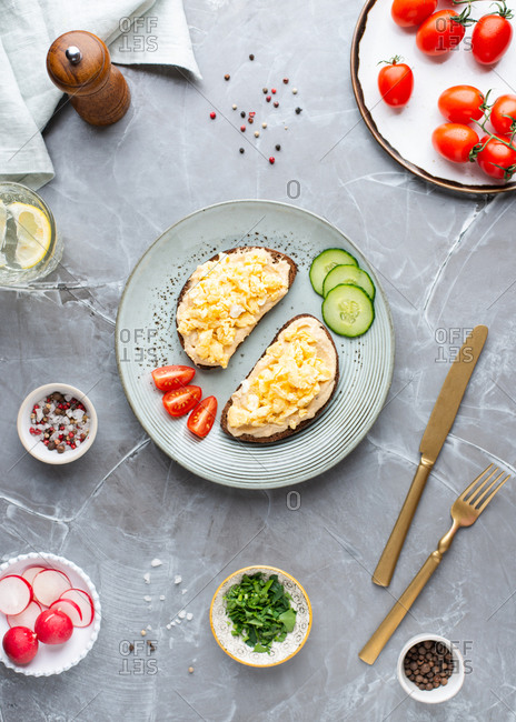 Overhead view of open face sandwiches with hummus and scrambled eggs served with fresh vegetables