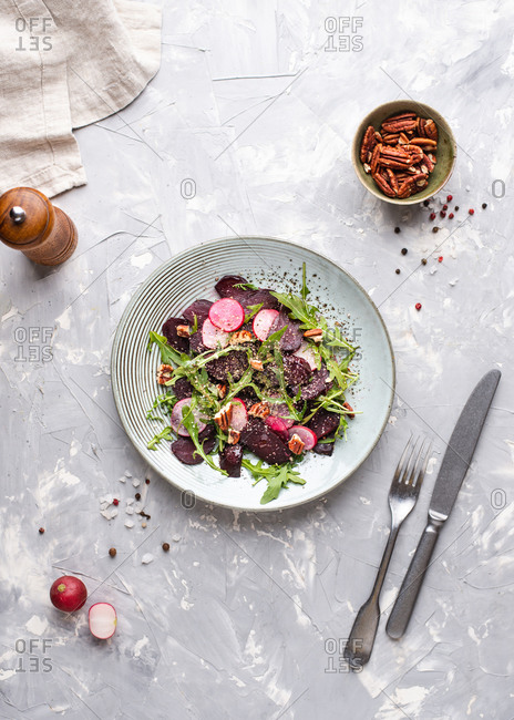 Overhead view of beetroot salad with arugula, pecan nuts and radish