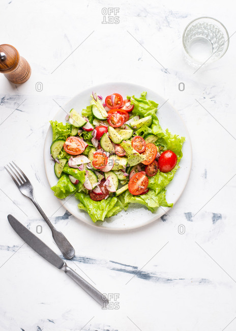 Overhead view of ceramic plate with vegetable salad with fresh tomatoes, cucumber and lettuce