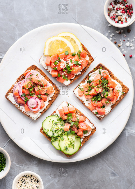 Overhead view of plate with open faced sandwiches with fish, vegetables and cream cheese