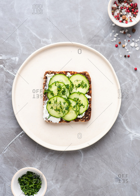 Overhead view of vegetarian open face sandwich with fresh cucumbers, cream cheese and dill