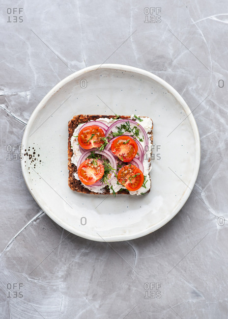 Overhead view of vegetarian open face sandwich with fresh tomatoes, cream cheese, dill and red onion