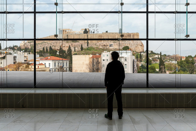 Silhouette of a man looking through a window the Acropolis of Athens in Greece