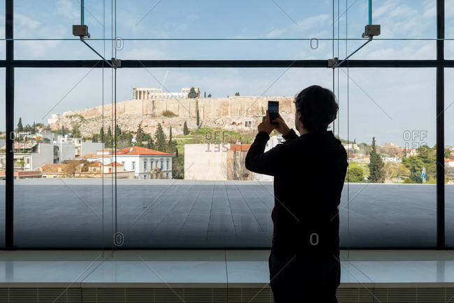 Silhouette of a man taking a photo through a window of the Acropolis of Athens in Greece
