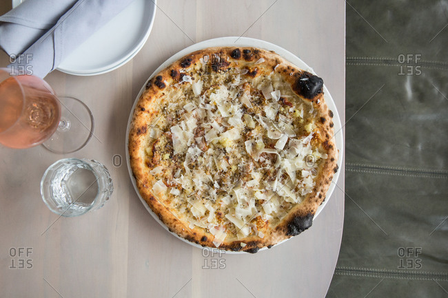 Overhead view of pizza served with rose wine in restaurant