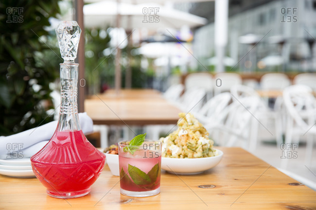 Pink cocktail and appetizers on wooden table