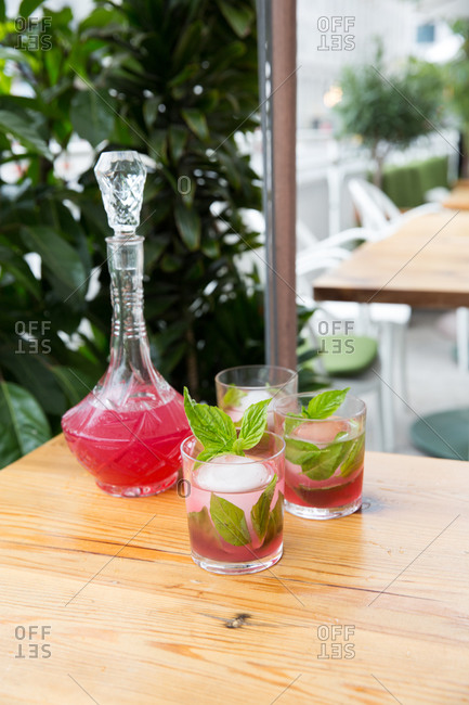 Pink cocktail with basil beside a crystal carafe on wooden table