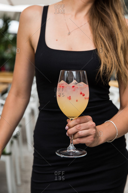 Woman wearing a black dress holding a cocktail at a restaurant