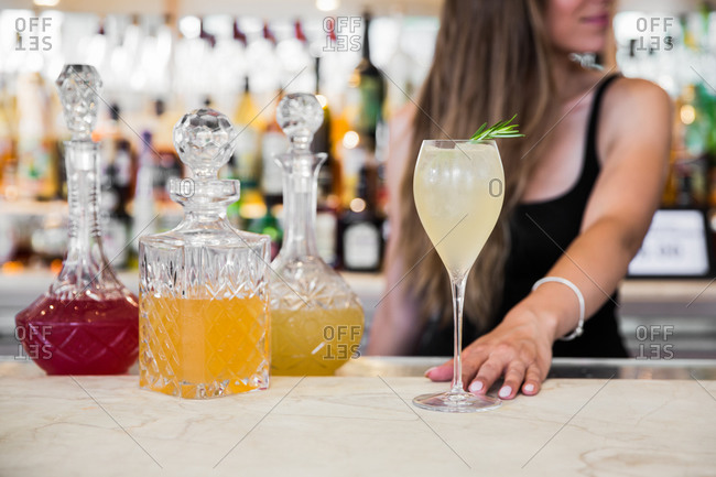 Female bartender sliding a cocktail onto bar with three fancy decanters
