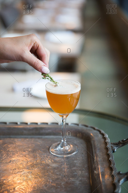 Woman placing thyme into cocktail on an antique tray