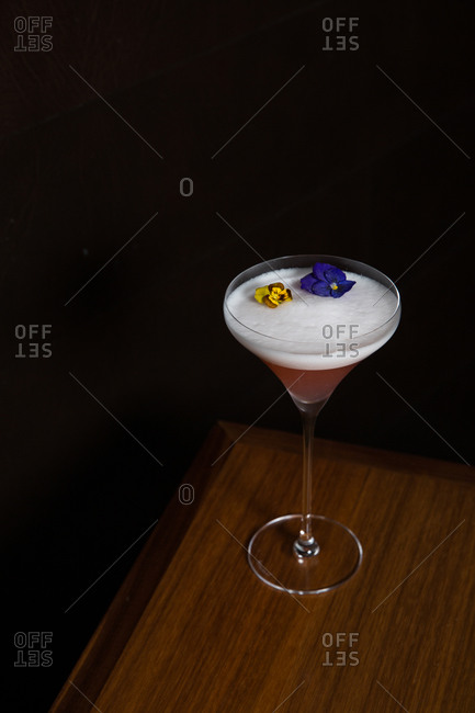 Pink foamy cocktail with edible flowers on wooden table