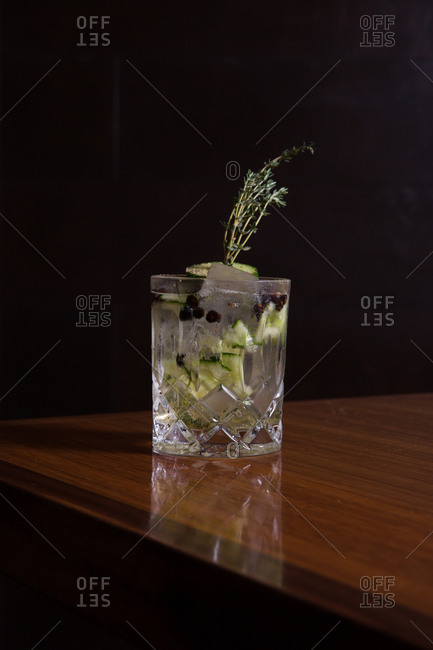 Cocktail with cucumber and thyme on a wooden table