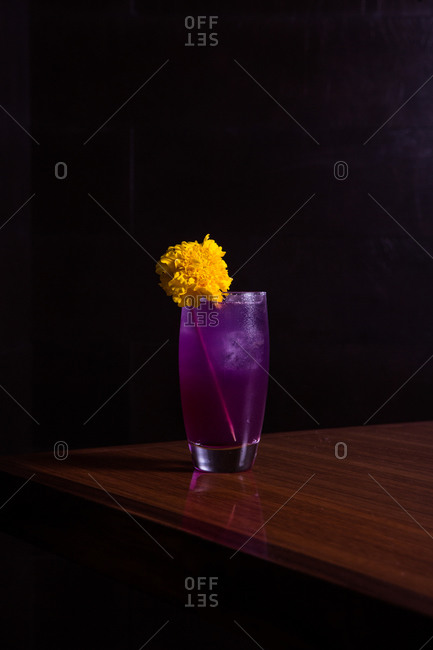 Purple cocktail with a large yellow flower