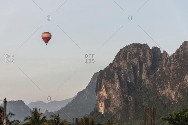 Hot air balloon over mountains in Vang Vieng, Laos