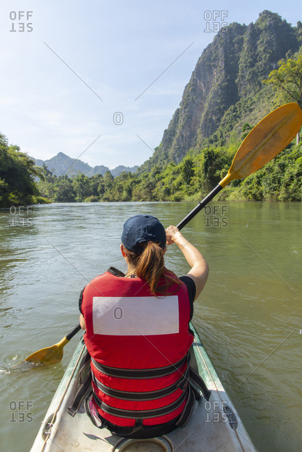 Rear view of woman kayaking the Nam Song River in Vang Vieng, Laos