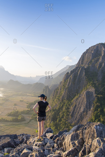 Hiker gazing over a valley from the top of a mountain near Vang Vieng, Laos